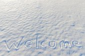 Word welcome written on the snow surface — Stockfoto