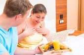 Female was pleasantly surprised by breakfast in bed — Stock Photo