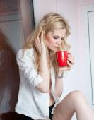 Portrait of a young blonde woman holding a red mug wearing a white shirt with an expression of being sadness. Fair hair  female posing indoor holding a big red cup of hot tea in her hands. — Stock Photo