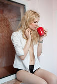 Portrait of a young, blond woman, holding a mug with both her hands, wearing a white shirt and black pants, with an expression of being sadness. Woman posing with a big red cup of tea. in her hands. — Stock Photo