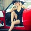 Summer portrait of stylish blonde vintage woman with long legs posing near red retro car. Fashionable attractive fair hair female near a red vintage vehicle. Sunny bright colors, outdoors shot. — Foto de Stock   #52303771