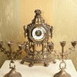 Golden vintage metallic clock with two candlesticks for three candles on white table. Luxurious art objects: ancient clock and candelabras. — Photo
