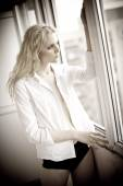 Attractive sexy blonde with white shirt looking on the window in daylight. Portrait of sensual long fair hair woman wearing blouse and black panties indoor scene. Beautiful long hair woman daydreaming — Stok fotoğraf