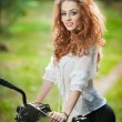 Beautiful girl wearing white lace blouse and black sexy shorts having fun in park with bicycle. Pretty red hair woman posing near her bike in a sunny day. Gorgeous curly redhead relaxing outdoor. — Stock Photo #53703013
