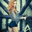 Beautiful girl wearing ultramarine blouse and black sexy shorts in park with bicycle. Pretty red hair woman posing near her bike. Side view of gorgeous curly redhead with creative makeup, outdoor. — Stock Photo #53703015