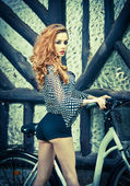 Beautiful girl wearing ultramarine blouse and black sexy shorts in park with bicycle. Pretty red hair woman posing near her bike. Side view of gorgeous curly redhead with creative makeup, outdoor. — Stock Photo