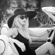 Outdoor summer portrait of stylish blonde vintage woman driving a convertible retro car. Fashionable attractive fair hair female with black hat in withe leather vehicle. Black and white outdoors shot. — Stock Photo #53734723