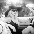 Outdoor summer portrait of stylish blonde vintage woman driving a convertible retro car. Fashionable attractive fair hair female with black hat in withe leather vehicle. Black and white outdoors shot. — Fotografia Stock  #53734725