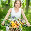 Beautiful girl wearing a nice white dress having fun in park with bicycle. Healthy outdoor lifestyle concept. Vintage scenery. Pretty blonde girl with retro look with bike and basket with flowers — Stock Photo #54179655