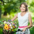 Beautiful girl wearing a nice white dress having fun in park with bicycle. Healthy outdoor lifestyle concept. Vintage scenery. Pretty blonde girl with retro look with bike and basket with flowers — Stock Photo #54179657