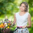 Beautiful girl wearing a nice white dress having fun in park with bicycle. Healthy outdoor lifestyle concept. Vintage scenery. Pretty blonde girl with retro look with bike and basket with flowers — Stock Photo #54179663