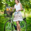 Beautiful girl wearing a nice white dress having fun in park with bicycle. Healthy outdoor lifestyle concept. Vintage scenery. Pretty blonde girl with retro look with bike and basket with flowers — Stock Photo #54179667