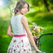Beautiful girl wearing a nice white dress having fun in park with bicycle. Healthy outdoor lifestyle concept. Vintage scenery. Pretty blonde girl with retro look with bike and basket with flowers — Stock Photo #54187555
