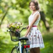 Beautiful girl wearing a nice white dress having fun in park with bicycle. Healthy outdoor lifestyle concept. Vintage scenery. Pretty blonde girl with retro look with bike and basket with flowers — Stock Photo #54187559