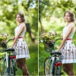 Beautiful girl wearing a nice white dress having fun in park with bicycle. Healthy outdoor lifestyle concept. Vintage scenery. Pretty blonde girl with retro look with bike and basket with flowers — Stock Photo #54187567