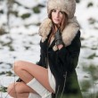 Portrait of young beautiful woman, outdoor shot in winter scenery. Sensual brunette girl with coat and fur cap posing in a park covered with snow. Fashionable female in a cold day. — Stockfoto