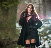 Portrait of young beautiful woman outdoor in winter scenery. Sensual brunette with long legs in black stockings posing fashionable in a park covered with snow. Attractive girl in black in winter shot — Stock Photo