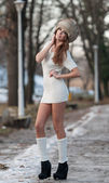 Portrait of young beautiful woman, outdoor shot in winter scenery. Sensual brunette girl in short white dress and fur cap posing in a park covered with snow. Fashionable female in a cold day — Stock Photo