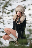 Portrait of young beautiful woman, outdoor shot in winter scenery. Sensual brunette girl with coat and fur cap posing in a park covered with snow. Fashionable female in a cold day. — Stock Photo