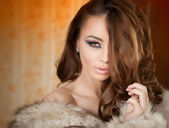Attractive sexy young woman wearing a fur coat posing provocatively indoor. Portrait of sensual female with creative makeup, studio shot. Beautiful girl covered only with a fur exposing her shoulders — Stock Photo