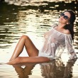 Young sexy brunette girl in wet white blouse posing provocatively in water. Sensual attractive woman with black sunglasses, summer shot. Long hair female with perfect body at beach during sunset. — Stock Photo #54230823