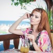 Attractive red hair young woman with bright colored blouse drinking lemonade on a terrace having blue sea in background. Gorgeous redhead model drinking fresh drink with straw in a summer day — Stock Photo #54230943