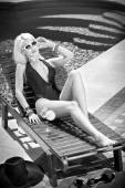 Beautiful sensual blonde with fashionable sunglasses relaxing at swimming pool with a juice. Attractive long fair hair woman in black low-cut swimsuit lying on sunbed, black and white summer shot. — Stock Photo