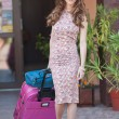 Beautiful woman with suitcases leaving the hotel in a big city. Attractive redhead with sunglasses and elegant dress on street carrying a suitcase. Young fashionable female with her luggage urban shot — Stock Photo #54655363