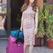 Beautiful woman with suitcases leaving the hotel in a big city. Attractive redhead with sunglasses and elegant dress on street carrying a suitcase. Young fashionable female with her luggage urban shot — Stock Photo #54655365