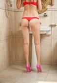Sexy beautiful body shoot of young woman wearing red lingerie and high heels in bathroom. Woman body with long legs in front of the mirror in elegant bath room. Rear view of woman perfect body. — Stock Photo