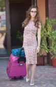 Beautiful woman with suitcases leaving the hotel in a big city. Attractive redhead with sunglasses and elegant dress on street carrying a suitcase. Young fashionable female with her luggage urban shot — Stock Photo