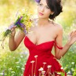 Young voluptuous brunette holding a wild flowers bouquet in a sunny day. Portrait of beautiful woman with low-cut red dress posing, outdoor shot. Provocative female enjoying the nature — Stock Photo #54721607