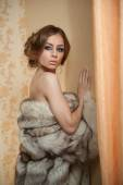 Attractive sexy young woman wearing a fur coat posing provocatively indoor. Portrait of sensual female with creative haircut, studio shot. Beautiful girl covered only with a fur exposing her shoulders — Stock Photo