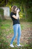 Attractive young girl taking pictures outdoors. Cute teenage girl in blue jeans and black t-shirt taking photos in autumnal park. Outdoor fall portrait of pretty teen having fun in park with camera — Stock Photo