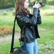 Attractive young girl taking pictures outdoors. Cute teenage girl in blue jeans and black leather jacket taking photos in autumnal park. Outdoor portrait of pretty teen having fun in park with camera — Stock Photo #55925627