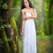 Lovely young lady wearing an elegant long white dress enjoying the beams of celestial light on her face in enchanted woods. Long hair brunette woman looking as a glamorous princess in the forest — Stock Photo #56163737