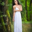 Lovely young lady wearing an elegant long white dress enjoying the beams of celestial light on her face in enchanted woods. Long hair brunette woman looking as a glamorous princess in the forest — Stock Photo #56163739