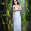 Lovely young lady wearing an elegant long white dress enjoying the beams of celestial light on her face in enchanted woods. Long hair brunette woman looking as a glamorous princess in the forest — Stock Photo #56163741