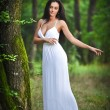 Lovely young lady wearing an elegant long white dress enjoying the beams of celestial light on her face in enchanted woods. Long hair brunette woman looking as a glamorous princess in the forest — Stock Photo #56163743