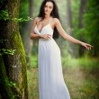 Lovely young lady wearing an elegant long white dress enjoying the beams of celestial light on her face in enchanted woods. Long hair brunette woman looking as a glamorous princess in the forest — Stock Photo #56163745