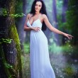 Lovely young lady wearing an elegant long white dress enjoying the beams of celestial light on her face in enchanted woods. Long hair brunette woman looking as a glamorous princess in the forest — Stock Photo #56163753