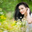 Beautiful young woman in wild flowers field.Portrait of attractive brunette girl with long hair relaxing in nature, outdoor shot in sunny day. Lady in white enjoying daisy field, harmony concept — Stock Photo #56164233