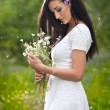 Young beautiful brunette woman holding a wild flowers bouquet in a sunny day. Portrait of attractive long hair female in white dress, outdoor shot. Side view of cute girl enjoying the nature in summer — Stock Photo #56164265