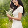 Young beautiful brunette woman holding a wild flowers bouquet in a sunny day. Portrait of attractive long hair female in white dress, outdoor shot. Side view of cute girl enjoying the nature in summer — Stock Photo #56164277