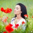 Young girl relaxing in green poppies field. Portrait of beautiful brunette woman posing in a field full of poppies. Beautiful woman enjoying the bright red wild flowers, harmony concept — Stock Photo #56164283