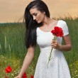 Young girl picking fresh poppies with cloudy sky in background. Portrait of beautiful brunette woman in a field full of poppies. Beautiful woman enjoying the bright red wild flowers, harmony concept — Stock Photo #56164295