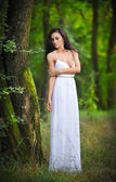 Lovely young lady wearing an elegant long white dress enjoying the beams of celestial light on her face in enchanted woods. Long hair brunette woman looking as a glamorous princess in the forest — Stock Photo