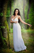 Lovely young lady wearing an elegant long white dress enjoying the beams of celestial light on her face in enchanted woods. Long hair brunette woman looking as a glamorous princess in the forest — Stock fotografie