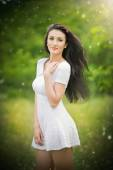 Beautiful young woman posing in a summer meadow. Portrait of attractive brunette girl with long hair relaxing in nature, outdoor shot in sunny day. Lady in white enjoying the nature, harmony concept — Stock Photo