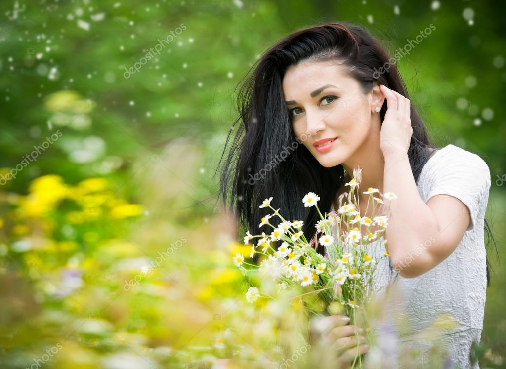 beautiful young woman in wild flowers field portrait of